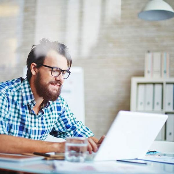 Handsome young businessman in casualwear networking on laptop